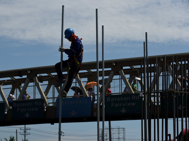 © Reuters. FILE PHOTO: A worker assembles a pole at a construction site of the Metro Rail Transit (MRT)