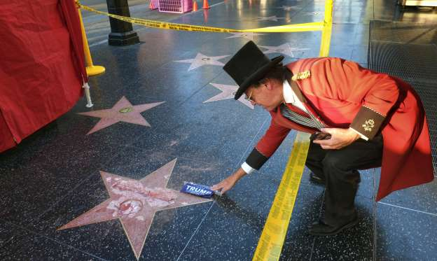 Gregg Donovan, who calls himself the unofficial ambassador of Hollywood, places a sticker for then-presidential candidate Donald Trump on Trump's vandalized star on the Hollywood Walk of Fame in October 2016.