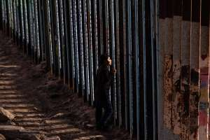 a group of people standing next to a fence: The decision bars the Trump administration from rapidly deporting such asylum seekers and represents another legal setback in President Donald Trump's battle to discourage migrants from trekking to the U.S.-Mexico border.