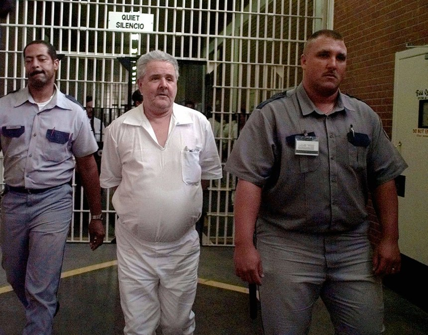 Confessed serial killer Henry Lee Lucas, center, is escorted back to his cell after talking with the media from a cage at the death row visitor area Wednesday, June 24, 1998, in Huntsville, Texas. On March 12, 2001, Lucas was found dead in prison from heart failure at age 64. (AP Photo/Pat Sullivan)