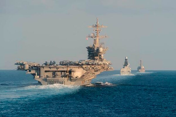The aircraft carrier Abraham Lincoln, British destroyer HMS Defender and the U.S. destroyer Farragut transit the Strait of Hormuz on Nov. 19. The Navy is trying to revamp its concept of operations away from clumping ships around aircraft carriers. (Navy photo by MC3 Zachary Pearson)