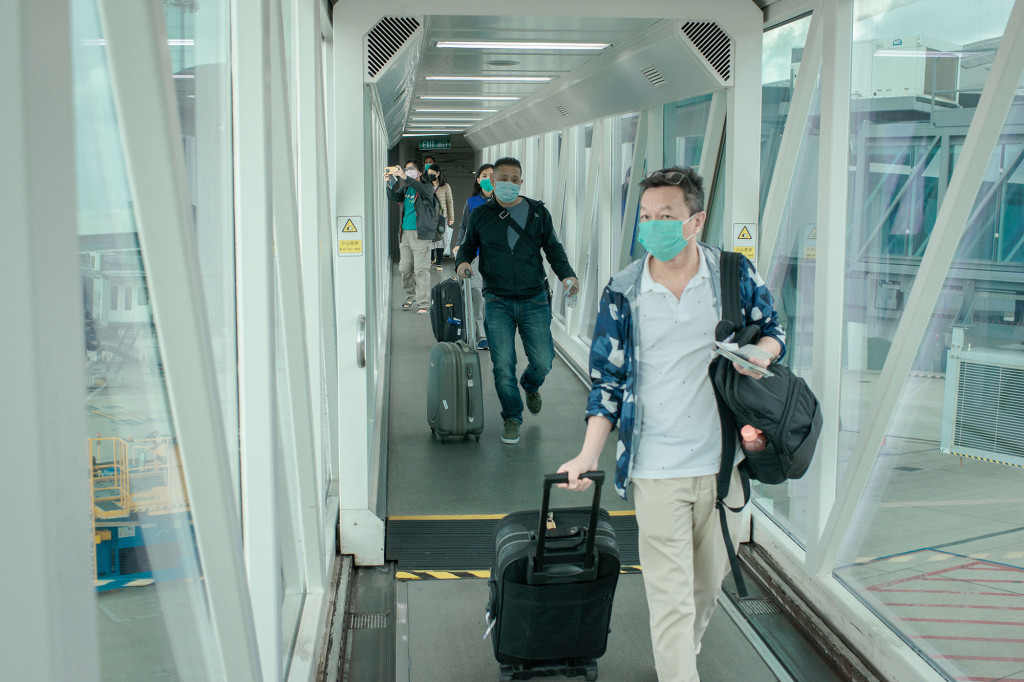 Passengers wear surgical masks at an airplane access bridge