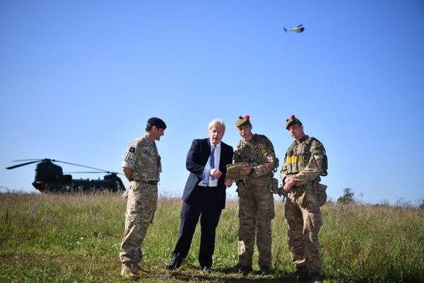 British Prime Minister Boris Johnson, second from left, flies a Black Hornet nano drone during a meeting with military personnel on Sept. 19, 2019, in Salisbury, England. (Ben Stansall/Getty Images)