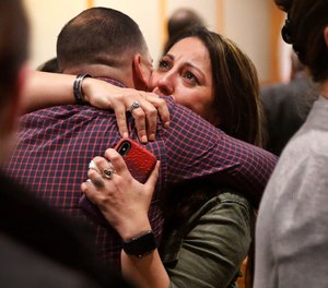Nicole Sherrard, facing, widow of fallen Richardson police Officer David Sherrard, is hugged by family and friends after convicted murderer Brandon McCall was given a death sentence. (Photo/AP)