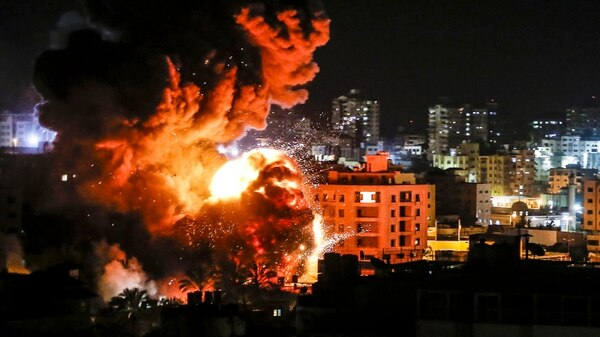 Fire and smoke billow above buildings in Gaza City during reported Israeli strikes on March 25, 2019. Israel's military had launched strikes on Hamas targets in the Gaza Strip, the army and witnesses said, hours after a rocket from the Palestinian enclave hit a house and wounded seven Israelis. (Mahmud Hams/AFP via Getty Images)